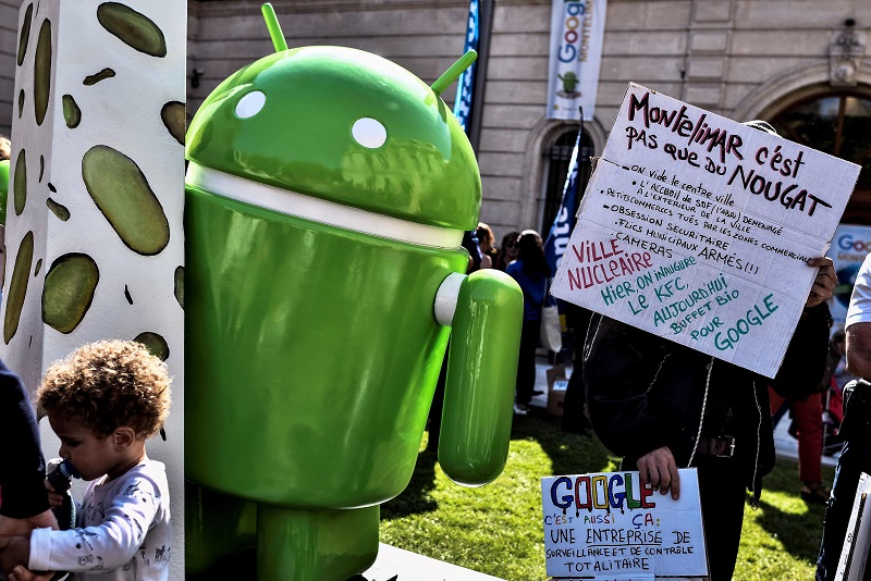 A person holds a sign reading 'Montelimar is not only nougat, we empty the city centre, we empty downtown, the reception of  homeless was moved to outside town, small businesses killed by commercial areas, security obsession, armed municipal police officers, cameras, nuclear city, yesterday we inaugurated the KFC today the organic buffet for Google' next to a statue donated by Google during its inauguration on September 21, 2016 in Montelimar, as Google decided to launch a new version of the android operating system called Android 7.0 or Nougat.  / AFP PHOTO / JEFF PACHOUD