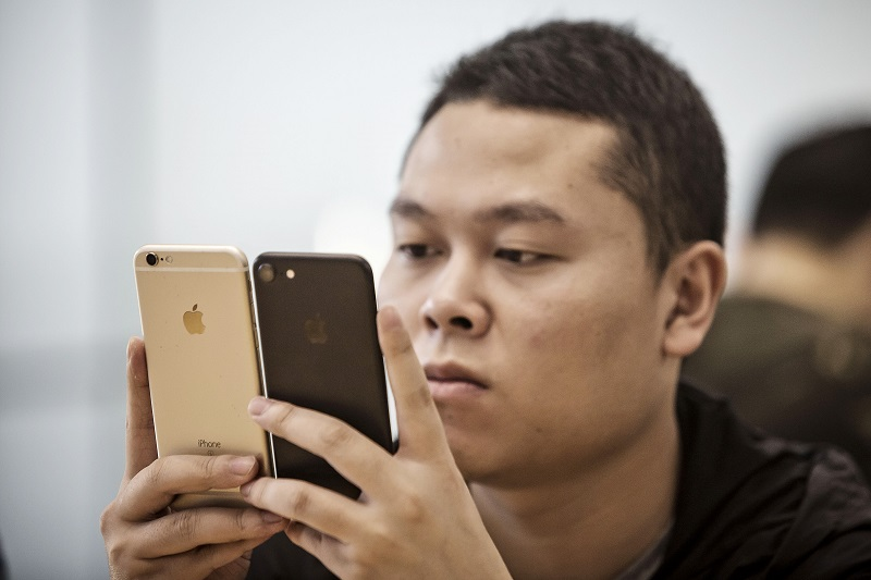 A customer inspects two Apple Inc. iPhone 7 smartphones at the Apple Store inside the IAPM shopping mall in Shanghai, China, on Friday, Sept. 16, 2016. Apple hopes its new iPhone 7 will help to stem a two-quarter decline in iPhone sales by enticing users to upgrade to the 7's faster processor and expanded memory options. Photographer: Qilai Shen/Bloomberg