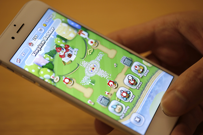 "The ""Kingdom Builder"" mode of Nintendo Co.'s Super Mario Run mobile game is displayed on an iPhone screen in this arranged photograph in Tokyo, Japan, on Monday, Dec. 19, 2016. Nintendo plummeted in Tokyo after the debut of Super Mario Run was met by lukewarm reviews. Photographer: Takaaki Iwabu/Bloomberg"